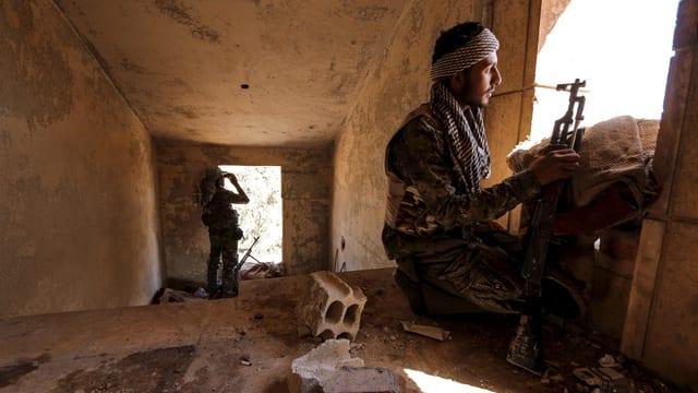 Bewaffnete Kämpfer in einem Gebäude schauen zu den Fenstern hinaus.