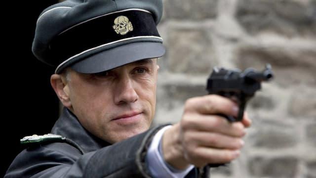 Christoph Waltz zielt mit einer Pistole
