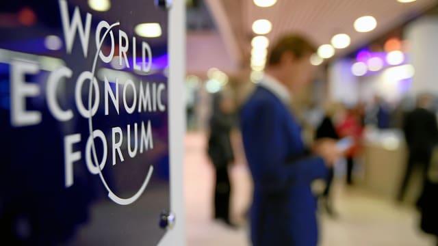 Teilnehmer am WEF 2015 guckt auf sein Handy.