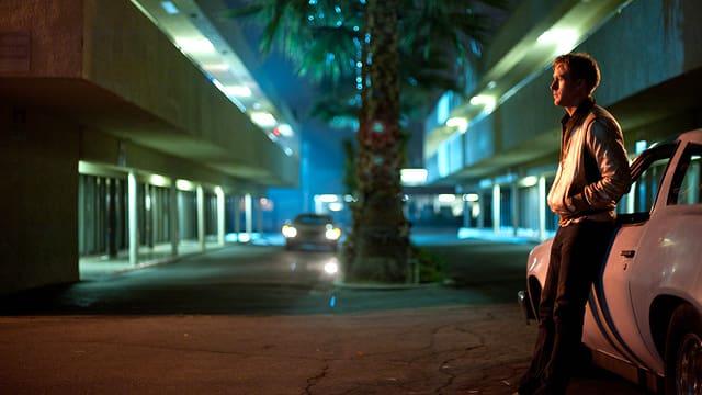 Ein Mann lehnt an ein weisses Auto, das in einer dunklen Strasse steht.