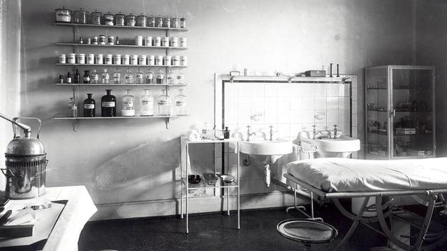 Historisches Bild: Behandlungszimmer mit Liege und Gestellt mit Medikamenten.