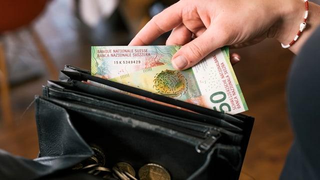 Frau nimmt Noten aus einem Geldbeutel