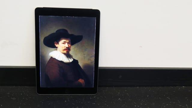 Ein Tabelt, auf dem ein Rembrandt-Porträt zu sehen ist, lehnt an einer Wand.