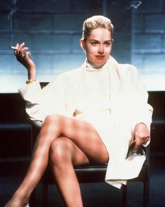 Sharon Stone mit überschlagenen Beinen auf Stuhl mit Zigarette
