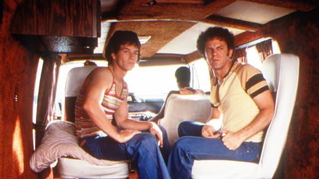 Zwei Männer sitzen auf der Rückbank eines Vans.