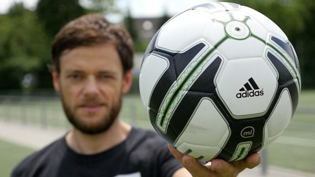 Ein Mann hält einen Fussball in die Kamera.