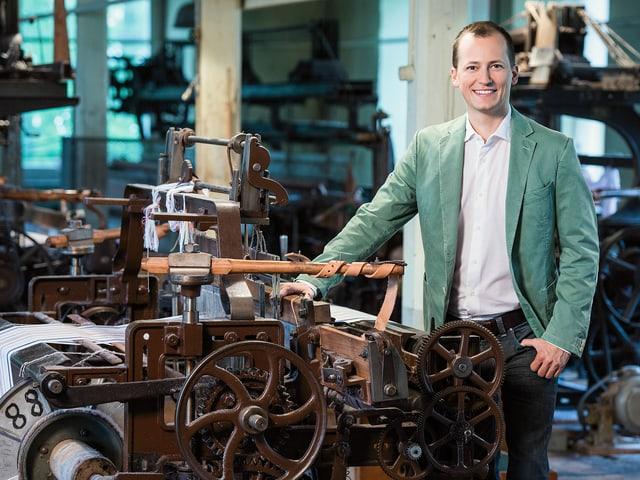 Porträtbild: Michael Weinmann in der Fabrik vor Webstuhl