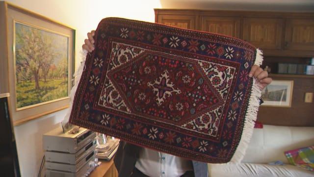Ein Teppichbetrüger versteckt sich hinter einem vorgehaltenen Teppich.
