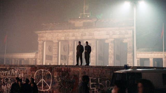 Berlin, Nov. 14, 1989: Zwei Sicherheitsleute auf der Berliner Mauer. Im Hintergrund ist das Brandenburger Tor zu sehen.