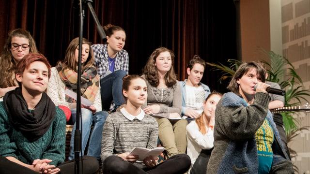 Rapperin Big Zis spricht ins Mikrofon, hinter ihr sitzen knapp zehn Schülerinnen.