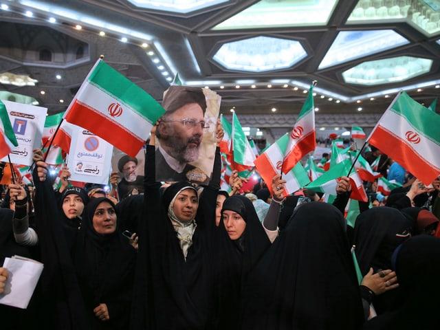 Frauen mit Flaggen und einem Porträtbild eines Mannes.