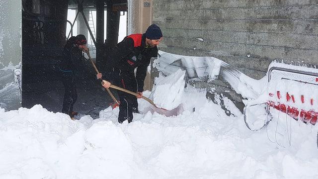 Zwei Männer schaufeln Schnee