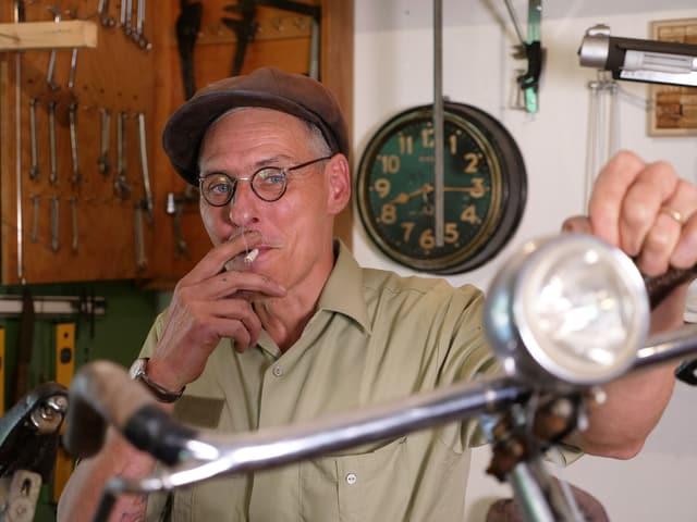 Ein rauchender Mann mit Mütze, seine linke Hand lehnt lässig auf einem alten Fahrradlenker.