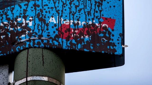 Das Logo am unteren Rand eines AfD-Plakats ist von schwarzen Farbspritzern fast verborgen.
