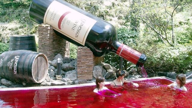 In einem Bad mit rotem Wasser sitzen drei junge Frauen. Hinter dem Bad ist eine riesige Weinflasche installiert, aus der das rote Wasser direkt ins Bad fliesst.