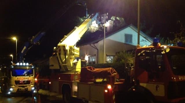 Zwei Feuerwehrautos mit Kran heben einen Baum von einem Hausdach.