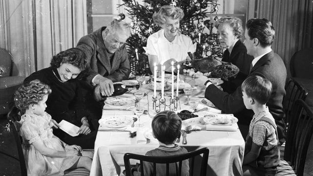 Schwarzweissbild: Eine grosse Familie vor einem Weihnachtsbaum am Esstisch