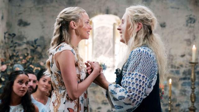 In einem alten Gebäude, Mutter und Tochter stehen sich gegenüber, halten sich bei den Händen und schauen sich ins Gesicht. Im Hintergrund Zuschauer.