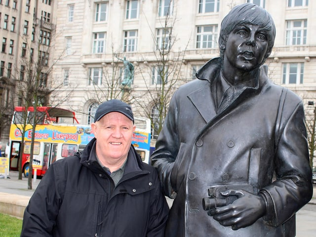 Ein Mann mit Mütze neben einer John-Lennon-Statue.