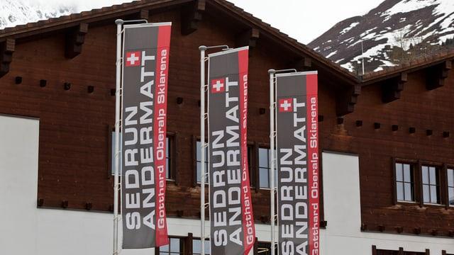 Fahnen des Skigebietes Andermatt-Sedrun flattern vor einem Haus in Andermatt