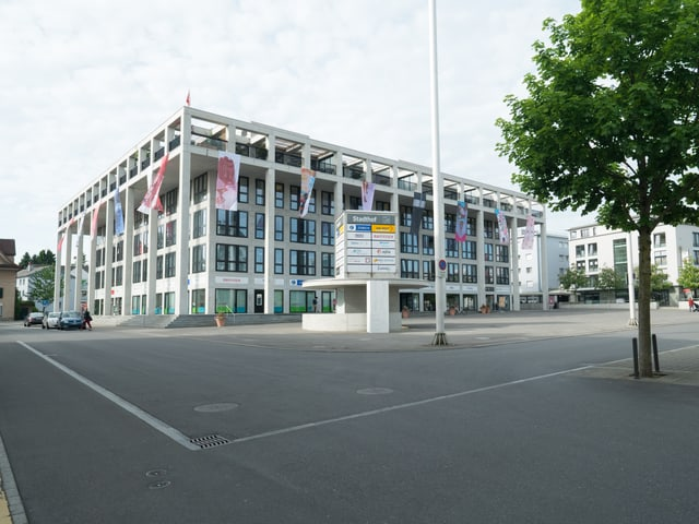 Moderner Bau an einem Platz mit Fahnen geschmückt.