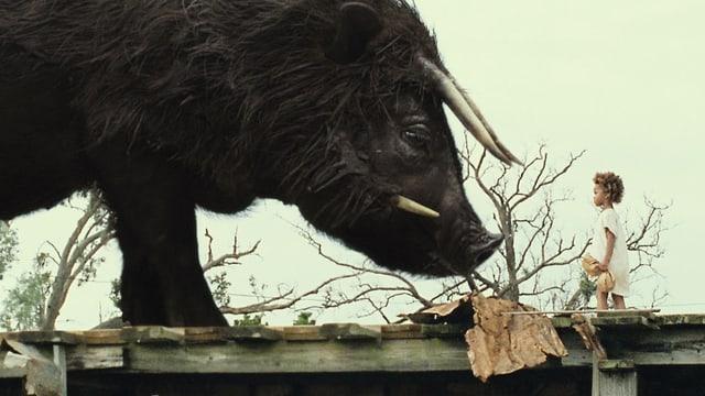 Die sechsjährige Hauptfigur Hushpuppy, steht vor einem riesigen Büffel.