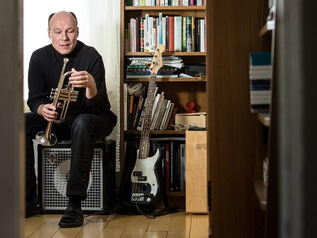 Dieter Ammann sitzt mit Instrumenten zwischen Bücherregalen