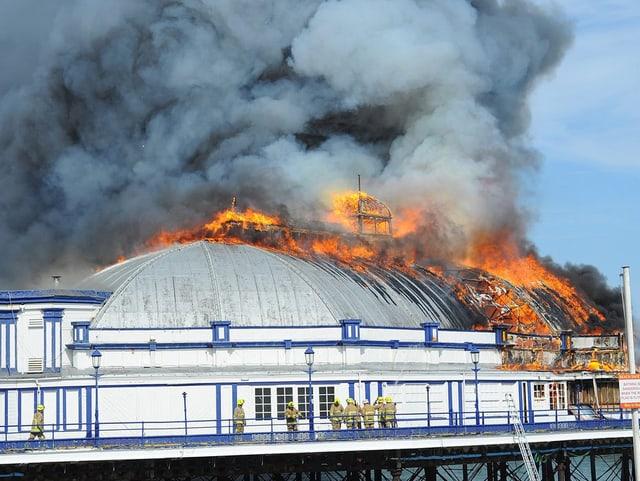 Ein Kuppelbau auf dem Pier brennt, viel Rauch steigt auf