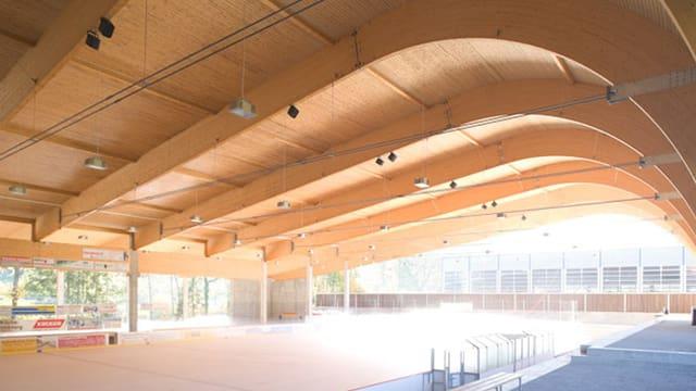 Kunsteisnbahn überdacht, mit einer grossen, ovalen Holzkonstruktion.