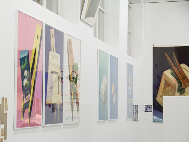 Nahaufnahme einer Plakat-Reihe an der Museumswand: Auf allen Bildern ist eine Wäscheklammer zu erkennen.