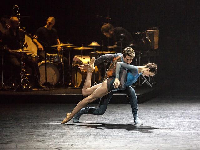 Tänzerin lehnt schräg über dem Boden gehalten von einem Tänzer.