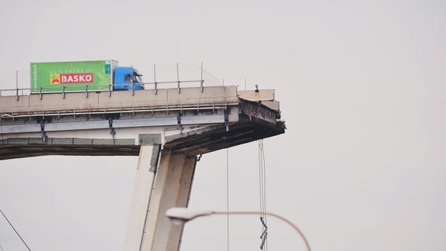 Grüner Lastwagen auf einer Brücke.