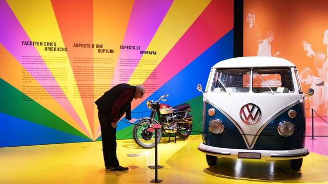 Ein Mann schaut sich einen VW-Bus in einem Ausstellungsraum an.