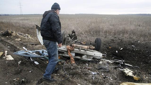 Ein Mann steht vor dem Wrack eines explodierten Autos, welches über eine Landmine gefahren ist.