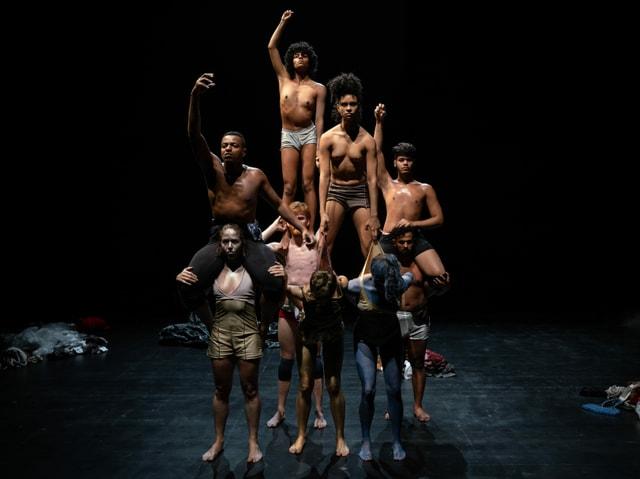 Menschen, halbnackt auf der Bühne in einer Menschenpyramide formiert.