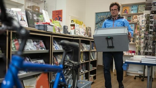 Daniel Stehelin trägt eine Kiste zum Velo.