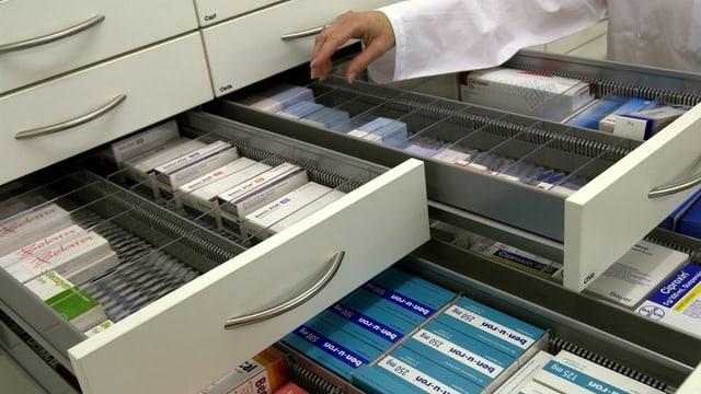 Eine Person öffnet verschiedene Medikamenten-Schubladen in einer Apotheke.