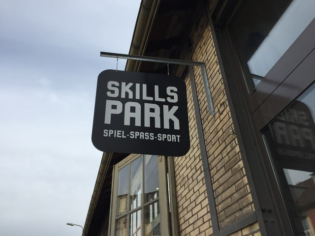 Ein schwarzes Schild mit Aufschrift Skillspark, montiert an einer Backsteinwand.