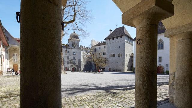 Blick auf einige alte Schlossgebäude aus der Ansicht eines Säulenganges.