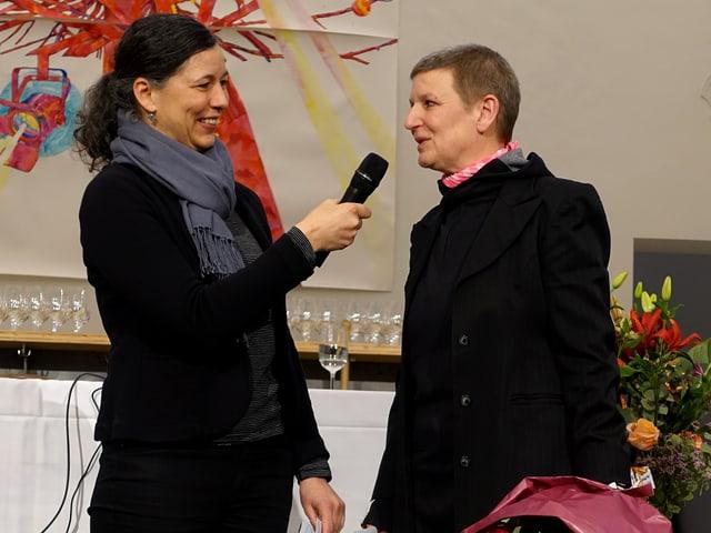 Zwei Frauen, stehend, eine hält einen Blumenstrauss und spricht in ein Mikrofon.