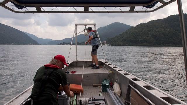 Zwei Männer auf einem Boot. Rechts der Monte San Giorgio.