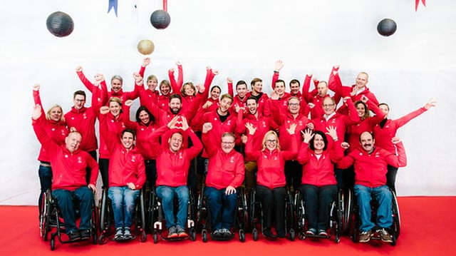 Viele Frauen und Männer, zum Teil in Rollstühlen, mit roten Jacken.