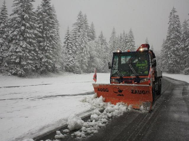 Ein Schneeräumungsfahrzeug räumt Schnee von der Strasse.