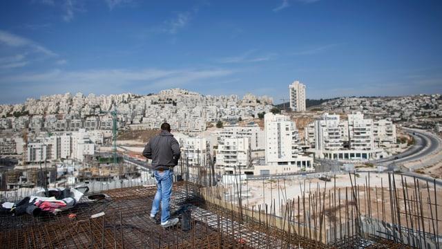 Baustelle mit Armierungseisen auf einem Hausdach, im Hintergrund eine jüdische Siedlung
