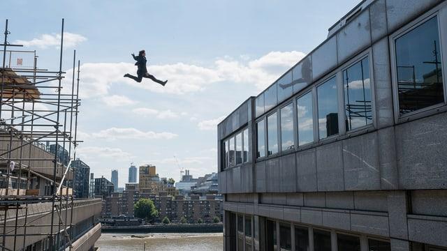 Tom Cruise springt vom einen Gebäude zum anderen.