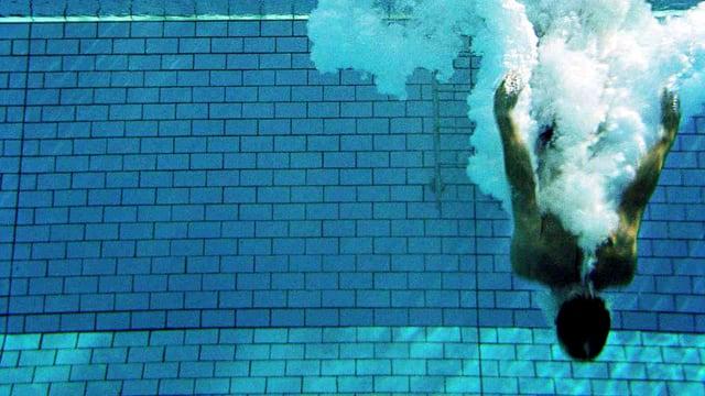 Eine Person taucht kopfüber in einen hellblau gekachelten Swimming Pool.