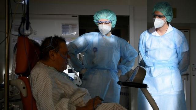 Patient mit Schlauch, eine Frau und ein Mann in Schutzkleidung