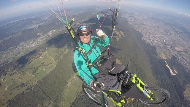 Rollstuhlfahrer mit Gleitschirm in der Luft.