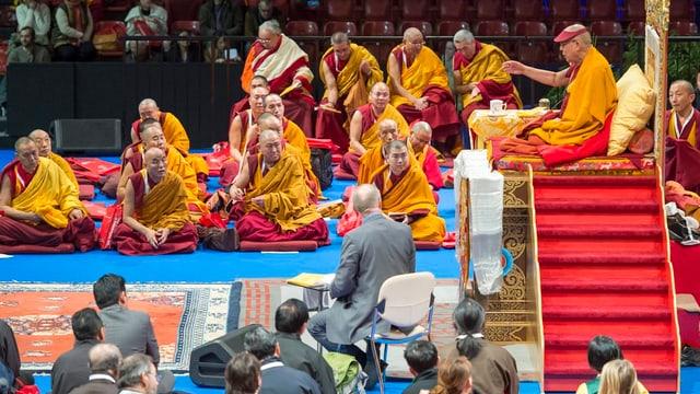Der Dalai Lama auf dem Thron, um ihn herum sitzen Mönche und Anhänger