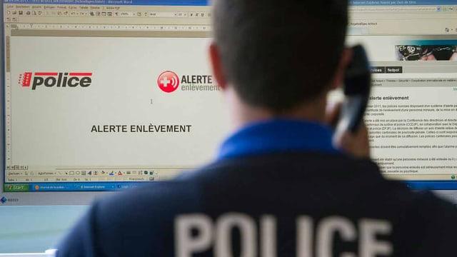 Ein Polizist sitzt vor dem Computer und telefoniert.